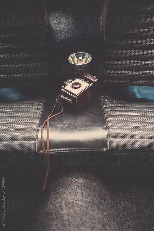 vintage camera on back seat of vintage car by Lisa MacIntosh for Stocksy United
