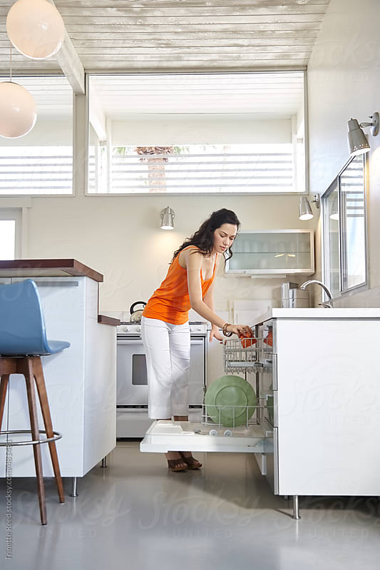 Hispanic woman loading the dishwasher by Trinette Reed for Stocksy United