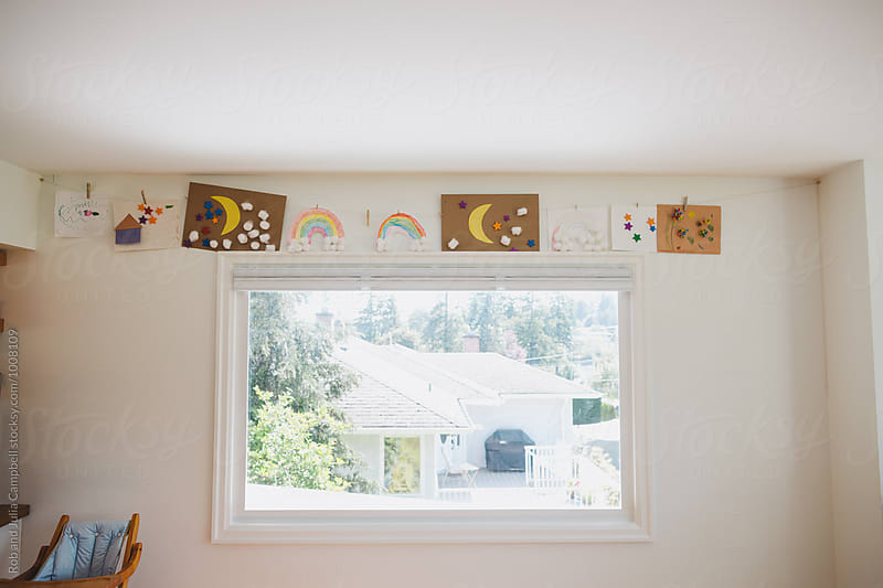 Kids artwork hanging on the wall by Rob and Julia Campbell for Stocksy United