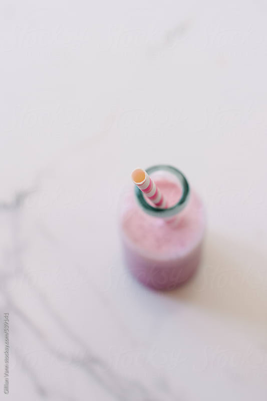 strawberry smoothie in a mini glass milk bottle by Gillian Vann for Stocksy United