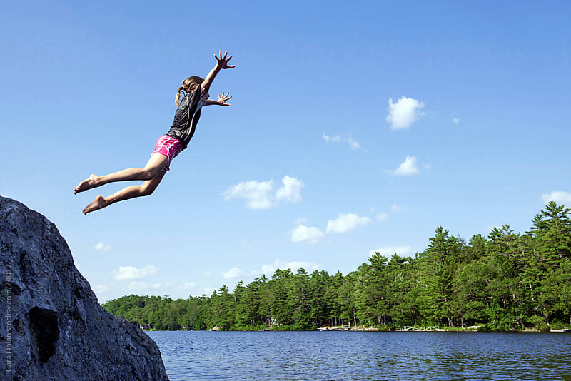 Girl flies off a giant boulder into lake water by Cara Dolan for Stocksy United