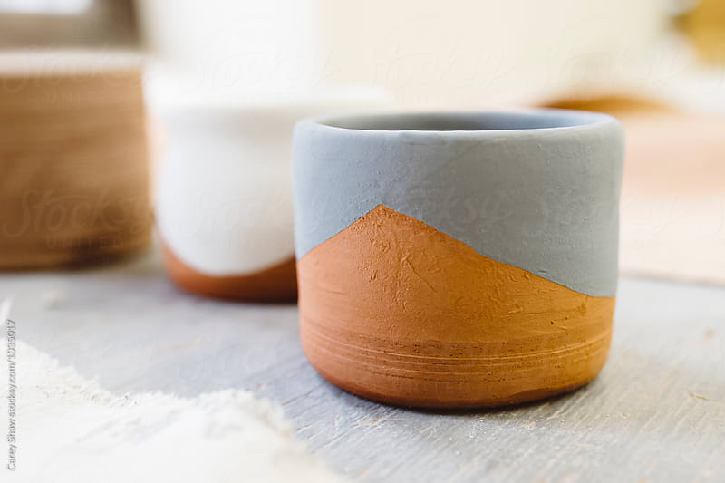 Terra cotta mugs with glaze designs by Carey Shaw for Stocksy United
