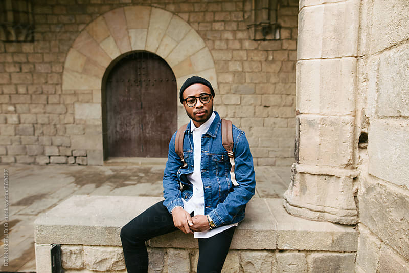 Portrait of an african american guy sitting in old town. by BONNINSTUDIO for Stocksy United