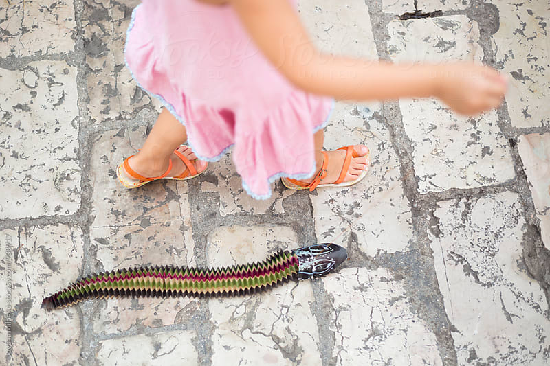 Little girl in pink dress pulling a snake toy trough the city by Jovana Milanko for Stocksy United