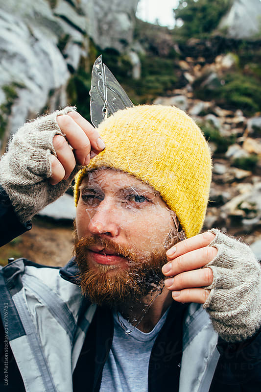 Bearded Man In Yellow Beanie Peering Through Broken Piece of Clear Ice by Luke Mattson for Stocksy United