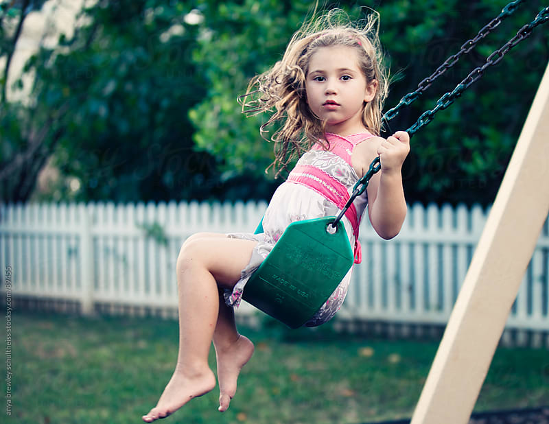 Portrait of a young girl with blond hair swinging at a park by anya brewley schultheiss for Stocksy United