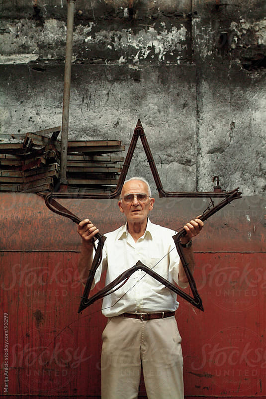 old man holding a star by Marija Anicic for Stocksy United