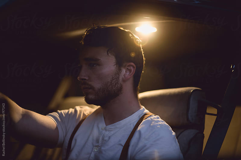 Handsome young man in automobile at twilight by Rachel Bellinsky for Stocksy United