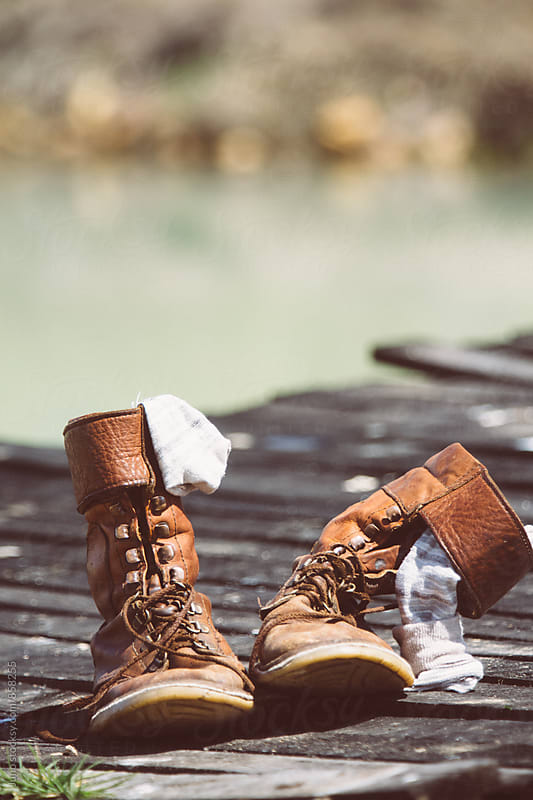 Old leather hiker boots on a wooden boardwalk by Micky Wiswedel for Stocksy United