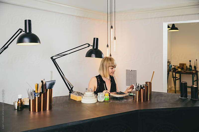 Young attractive jewelry designer working in her studio by Lior + Lone for Stocksy United