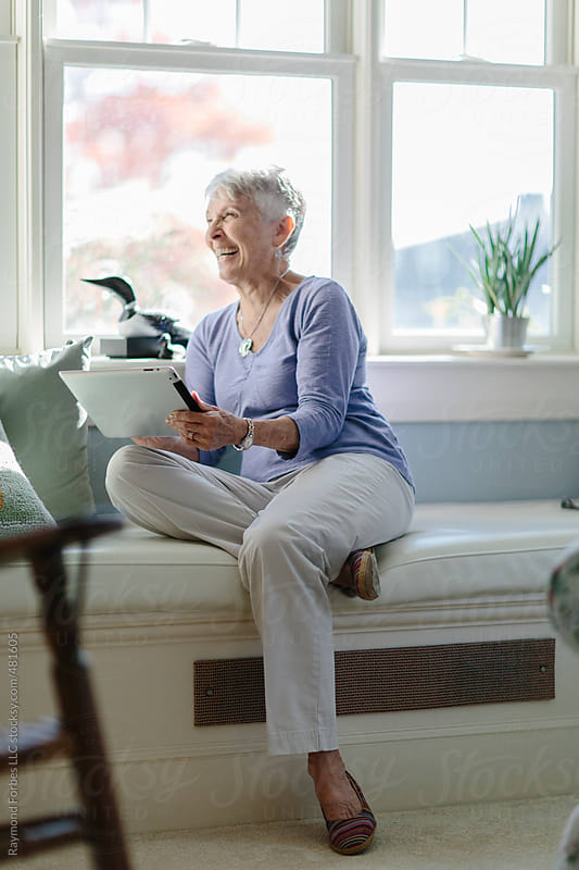 Senior Woman working on mobile computer at Home by Raymond Forbes LLC for Stocksy United