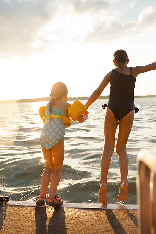 Sisters jumping off boat platform into a lake in the evening by Amanda Worrall for Stocksy United