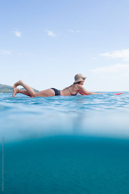 surfer paddles out on her surfboard by Melchior van Nigtevecht for Stocksy United