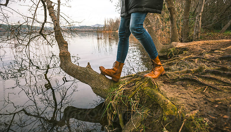 Woman wearing leather boots on lakeshore. Banyoles Lake, Spain. by BONNINSTUDIO for Stocksy United