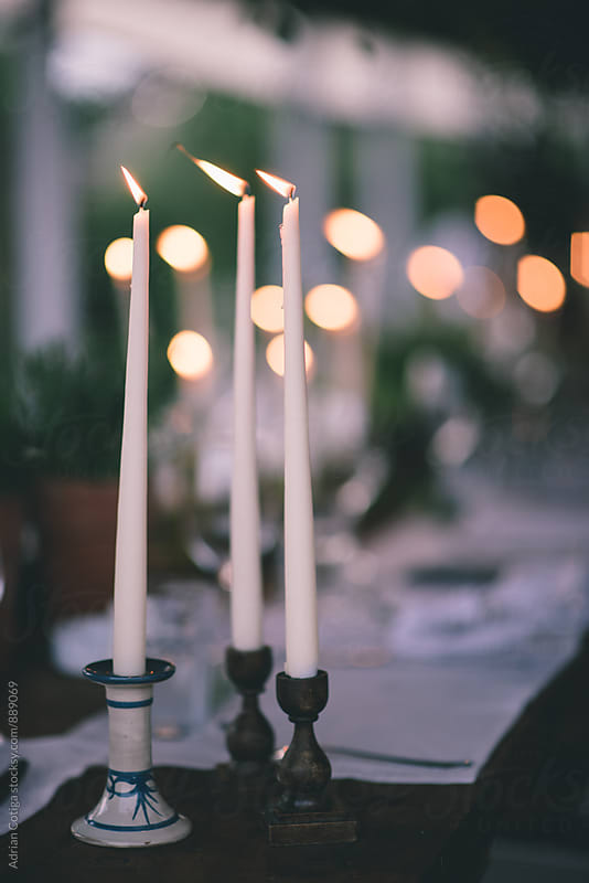 Table decorated with candles; Candles centerpiece for a a fancy dinner party by Adrian Cotiga for Stocksy United