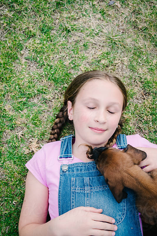 girl and her puppy enjoying a quiet moment together by Gillian Vann for Stocksy United