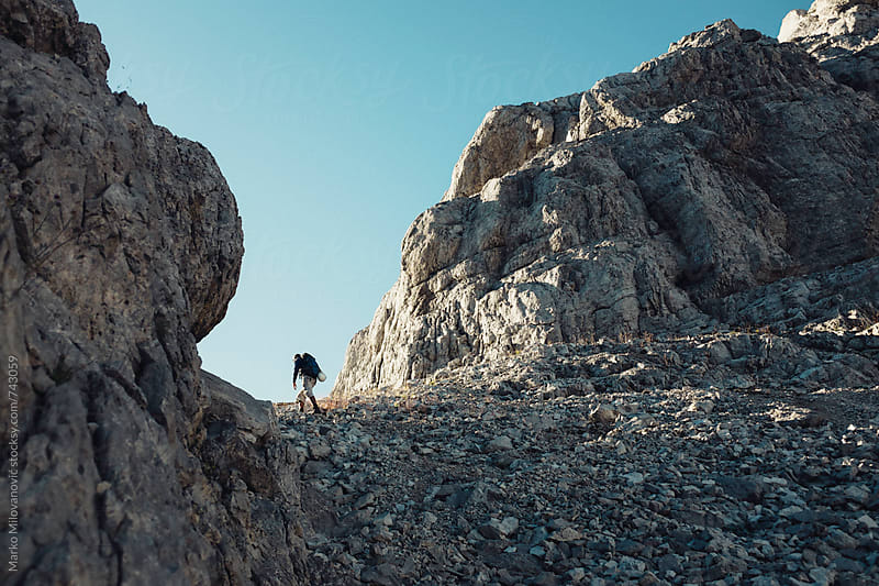 Mountaineer hiking alone in the rocky mountains by Marko Milovanović for Stocksy United