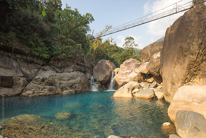 A water pool with a chain rope bridge. by Mike Marlowe for Stocksy United