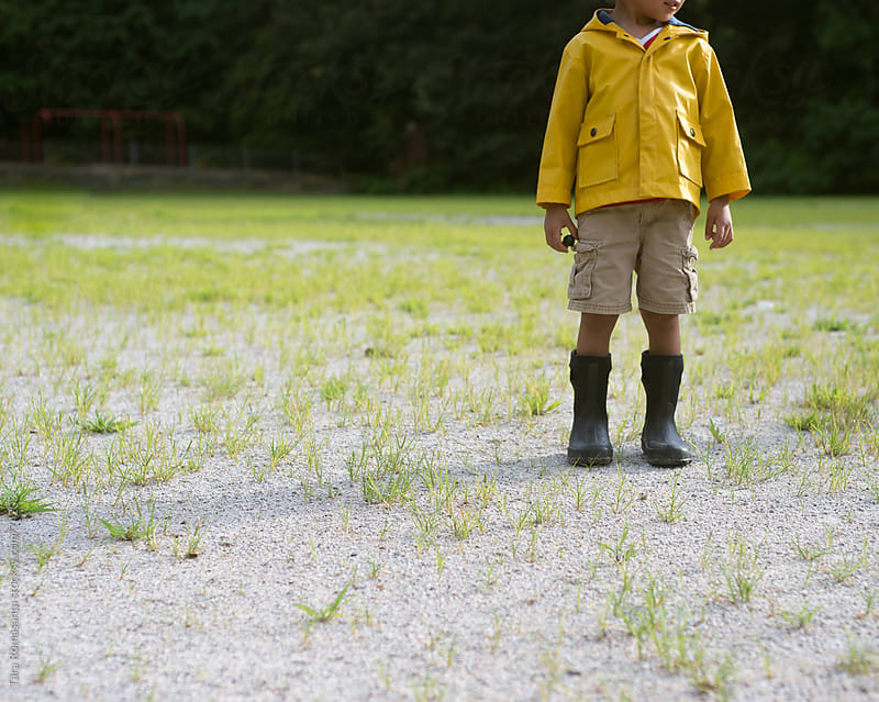 boy in rain jacket stands in a field as if looking for the puddle by Tara Romasanta for Stocksy United
