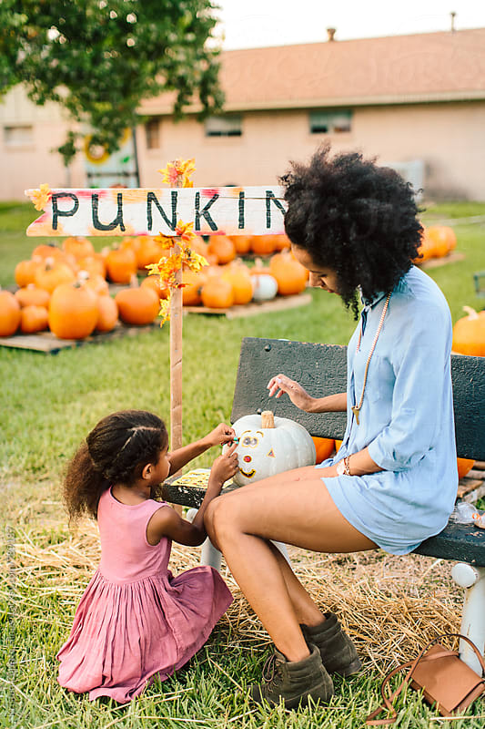 A littel girl and her mother decorating a pumpkin with stickers by Kristen Curette Hines for Stocksy United