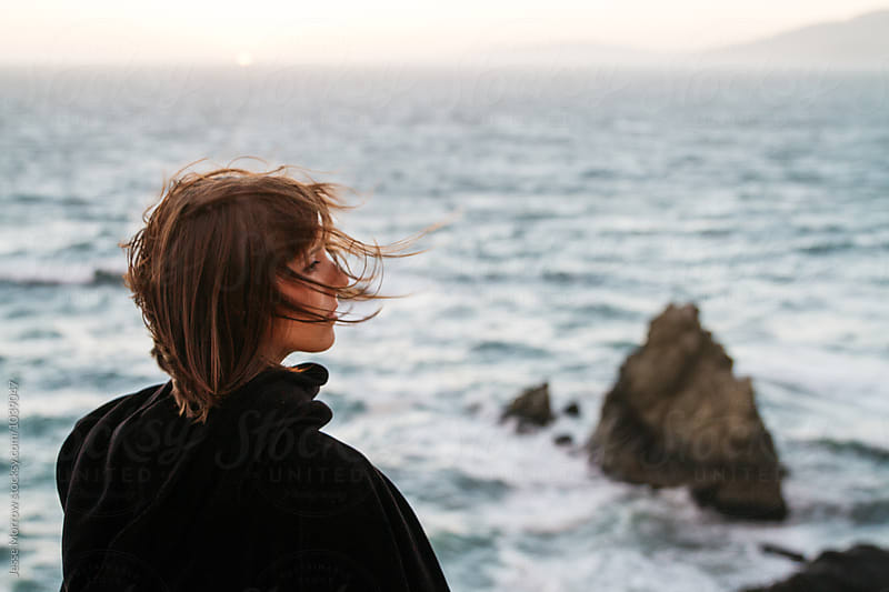 young woman with hair blowing at coast during sunset by Jesse Morrow for Stocksy United