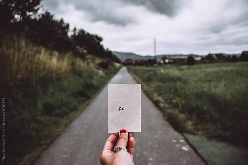 hand hoding a message behind a mountain road by Thais Ramos Varela for Stocksy United