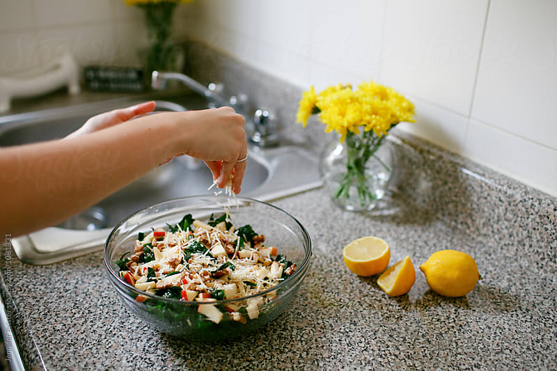 woman sprinkles cheese on salad  by Jennifer Brister for Stocksy United
