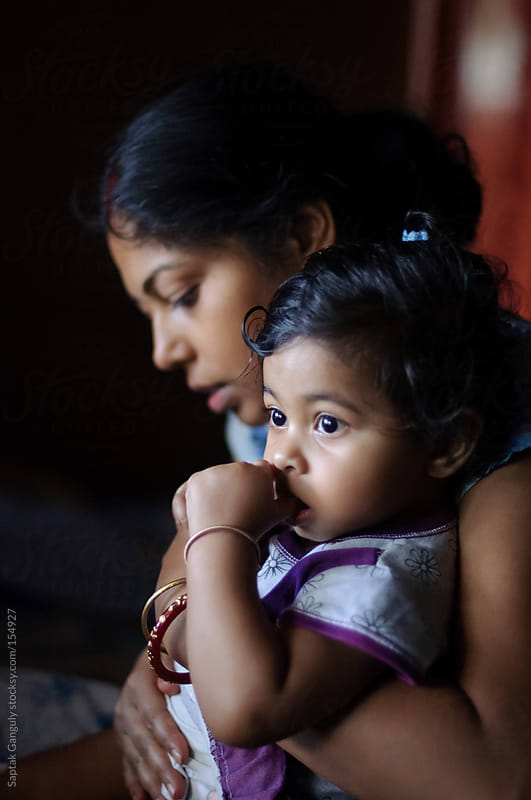 Toddler sitting on her mother's lap and sucking thumb by Saptak Ganguly for Stocksy United