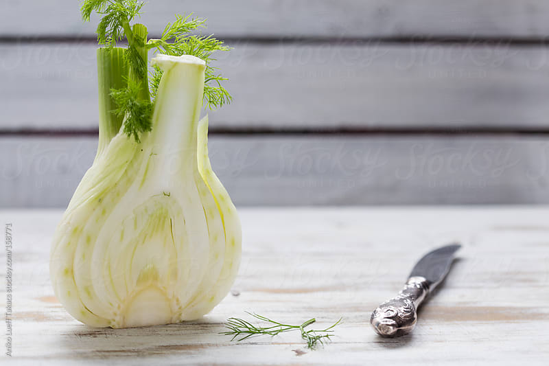 Halved fennel bulb with a knife by Aniko Lueff Takacs for Stocksy United