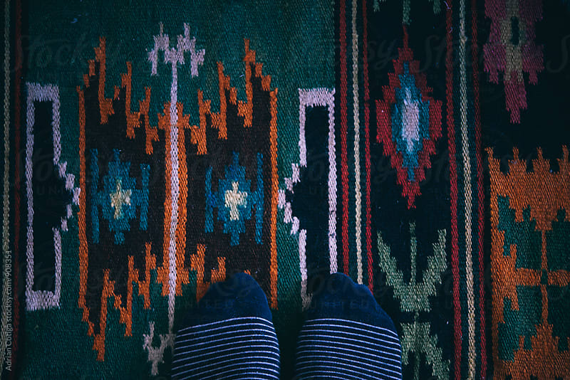 Striped socks on a carpet by Adrian Cotiga for Stocksy United