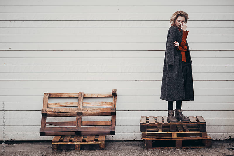 Beautiful woman in a grey coat against a white wall by Maja Topcagic for Stocksy United