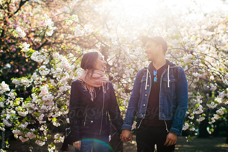 Young couple having fun in a park. by BONNINSTUDIO for Stocksy United