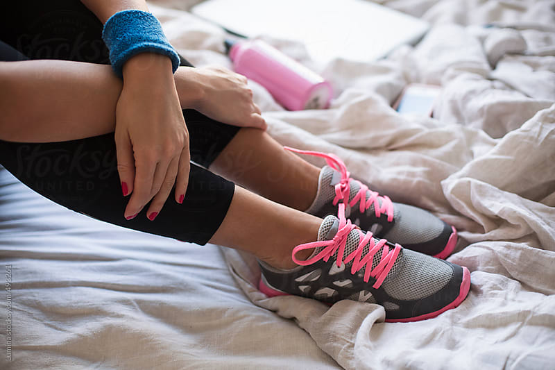 Woman in Running Tights and Trainers Sitting on the Bed by Lumina for Stocksy United