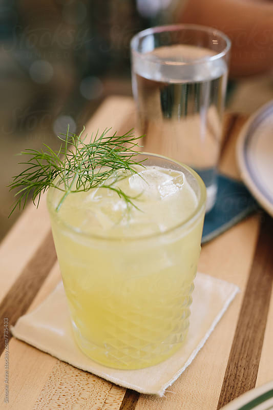 Yellow cocktail with dill by Simone Anne for Stocksy United