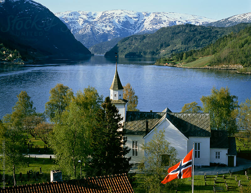 Church and Norwegian flag infront of Ulvikfjord. Hordaland. Norway. by Hugh Sitton for Stocksy United