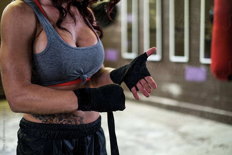 An attractive woman wrapping her hands preparing to box by Riley Joseph for Stocksy United