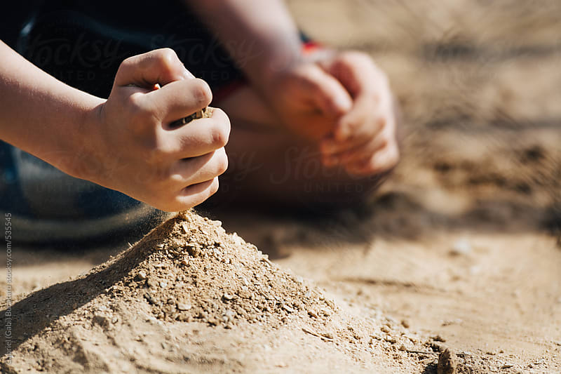 Young boy playing with his hands in the sand by Gabriel (Gabi) Bucataru for Stocksy United