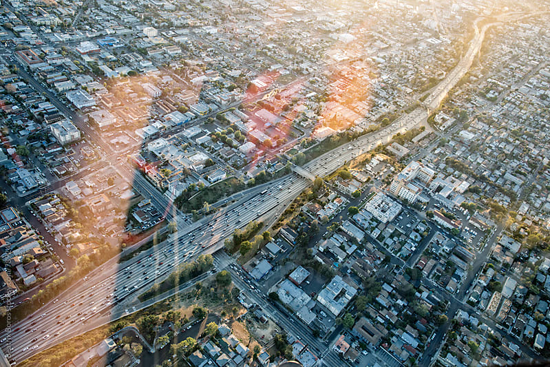 Freeway diagonally passing through the photo, cityscape with reflection captured at sunset by Beatrix Boros for Stocksy United