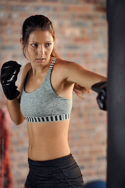 Fitness muscular lean female Punching A Bag With Boxing Gloves On by Daxiao Productions for Stocksy United