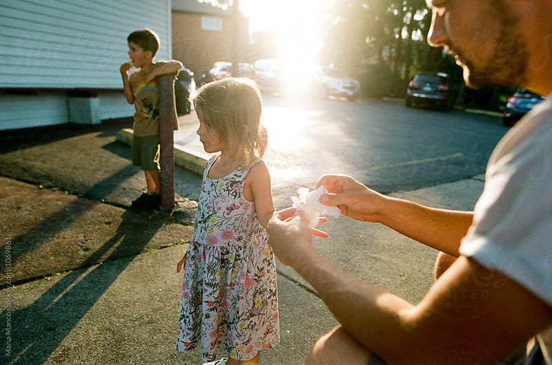 dad wipes little girls hands by Maria Manco for Stocksy United