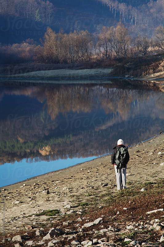 Woman standing near lake by Pixel Stories for Stocksy United