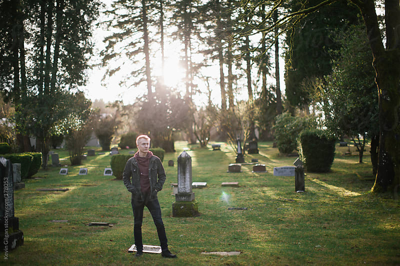 Young Man Stands in Graveyard by Kevin Gilgan for Stocksy United