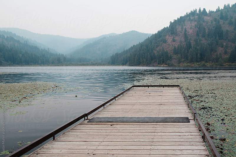 Dock on lake with smoky skies.  by Justin Mullet for Stocksy United