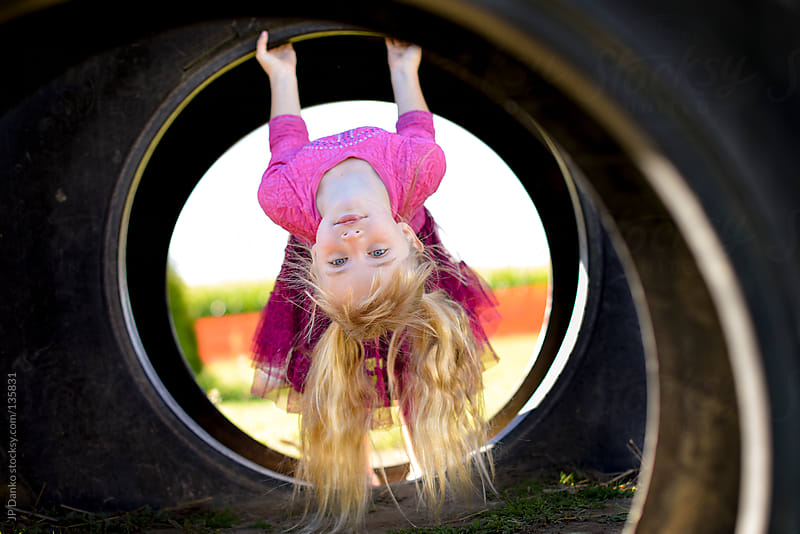 Little Girl Hanging Upside Down Playing at Park Outdoors by JP Danko for Stocksy United