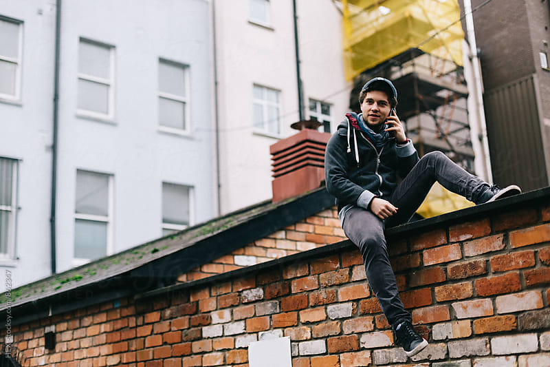 Young Man Standing on a High Wall in the City by HEX . for Stocksy United