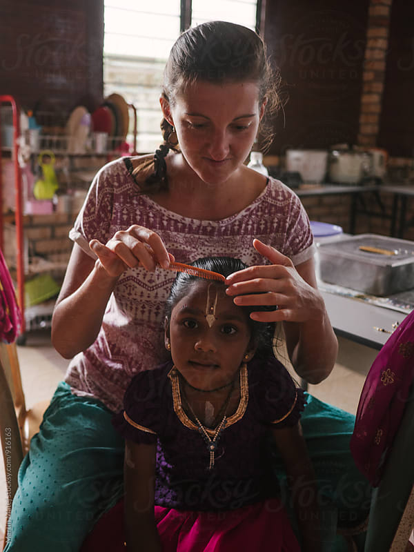 Young caucasian mum making hair of her adopted indian child by Martin Matej for Stocksy United