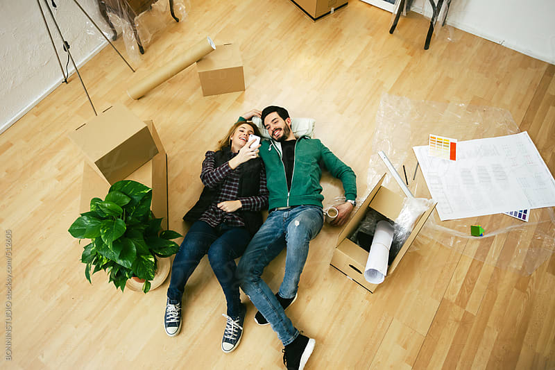 Young couple using smartphone in the new home.  by BONNINSTUDIO for Stocksy United