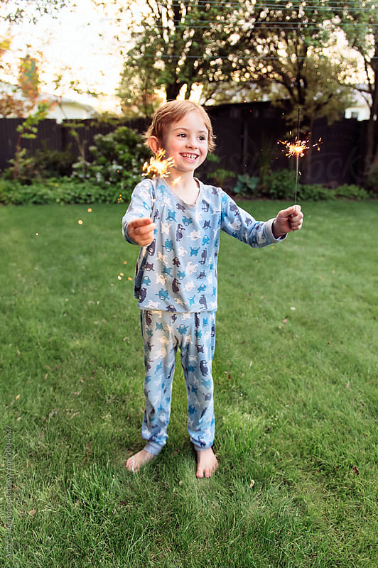 Happy child in pajamas excitedly holds out sparklers in each hand by Angela Lumsden for Stocksy United