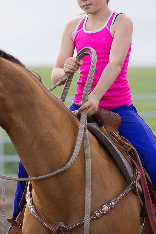 girl holding reins while sitting in saddle by Tana Teel for Stocksy United