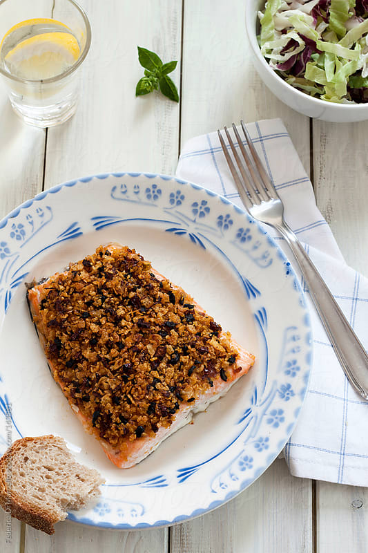 Salmon fillet with dried tomatoes and black olives by Federica Di Marcello for Stocksy United